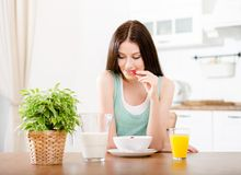 Girl eating strawberry with milk and orange juice Royalty Free Stock Photo