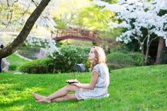 Girl eating sushi in cherry blossom garden Stock Photos