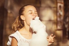 Girl eating sweet cotton candy Stock Photography