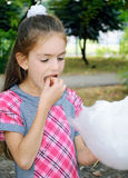 Girl eating sweet cotton wool Royalty Free Stock Image