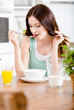 Girl eating tasty cereals and orange juice. Portrait of the girl eating tasty cereals with milk and citrus juice sitting at the kitchen table Stock Photo