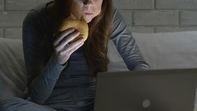 Girl eating unhealthy hamburger in front of laptop at night, fast food addiction. Stock footage stock footage