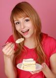 Girl eating vanilla cake Stock Image
