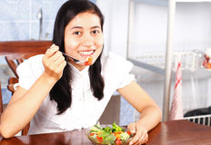 Girl eating vegetable  salad Stock Images