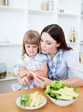 A girl eating vegetables with her mother Royalty Free Stock Image