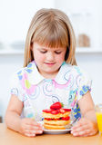 Girl eating waffles with strawberries Stock Image