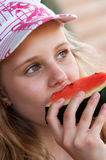 Girl eating watermelon. Portrait of a young girl eating watermelon royalty free stock images