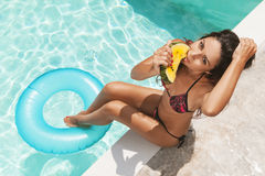 Girl eating watermelon against swimming pool Royalty Free Stock Photos