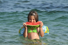 Girl eating watermelon on seashore Royalty Free Stock Image