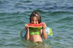 Girl eating watermelon on seashore. Food,fruits Royalty Free Stock Image