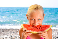 Girl eating watermelon on seashore or beach Royalty Free Stock Image
