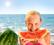 Girl eating watermelon on seashore or beach Stock Image