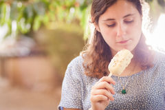Girl eating a white chocolate and almond ice-cream Stock Images