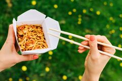 Girl eating wok noodles with vegetables in carton box to go, with bamboo chopsticks, closeup