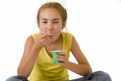 Girl eating yoghurt II Royalty Free Stock Photography