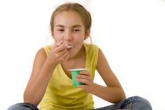 Girl eating yoghurt II. The nice girl eating yoghurt Royalty Free Stock Photography