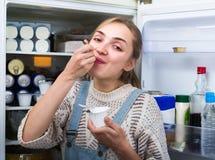 Girl eating yoghurt near fridge Stock Photos