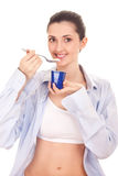 Girl eating yogurt. Young woman eating yogurt, smiling, isolated on white Royalty Free Stock Photos