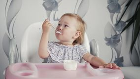 Girl eating yogurt on kitchen, little baby kid food, child eating with spoon Royalty Free Stock Image