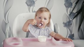 Girl eating yogurt on kitchen, little baby kid food, child eating with spoon royalty free stock photography