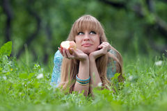 The girl eats an apple. The girl lies in a grass and eats an apple Royalty Free Stock Photo