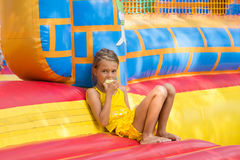 Girl eats an apple sitting on edge of the inflatable trampoline in amusement park Royalty Free Stock Photo