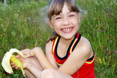 The girl eats a banana and laughs Royalty Free Stock Photography
