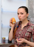 The girl eats cake near the refrigerator Stock Photography