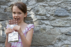 Girl eats chocolate. Seven year old girl eats chocolate Royalty Free Stock Photo