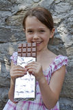 Girl eats chocolate. Seven year old girl eats chocolate Royalty Free Stock Photography