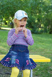 Girl eats chocolate. Little girl sits on the bench and eats chocolate outdoor Royalty Free Stock Photography
