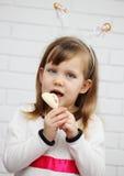 Girl eats chocolate heart Stock Images