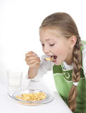 Girl eats corn-flakes with milk Royalty Free Stock Images