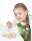 Girl eats corn-flakes with milk Royalty Free Stock Photography
