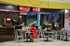 Girl eats at fast food restaurant Shanghai China. Shanghai, China - February 17, 2013: A young woman plays with her phone during a meal at a Carl's Jr. fast food Royalty Free Stock Images