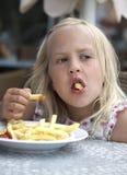 Girl eats fried potatoes Stock Image