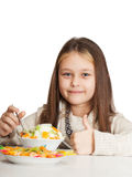 Girl eats fruit dessert and shows thumb Stock Photo