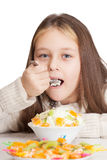 Girl eats fruit dessert spoon while sitting at a table Royalty Free Stock Images