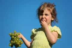 Girl eats grape against blue sky Royalty Free Stock Image