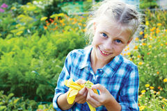 Girl eats green peas in the garden Royalty Free Stock Images