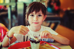Girl. Eats ice cream in the children of coffee Stock Photography