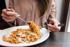 Girl eats Italian pasta with tomato, meat. Close-up spaghetti Bolognese wind it around a fork with a spoon. Parmesan Stock Images
