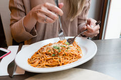 Girl eats Italian pasta with tomato, meat. Close-up spaghetti Bolognese wind it around a fork with a spoon. Parmesan Stock Photography