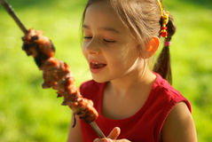 The girl eats a  kebab. The little girl with pleasure eats a shish kebab Royalty Free Stock Image