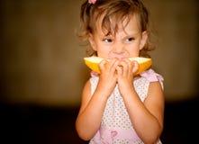 Girl eats melon. Little girl eats piece of juicy yellow melon Royalty Free Stock Image