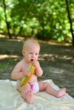 The girl eats a melon on a picnic. Little girl in the forest is eating melon royalty free stock images