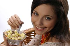 Girl eats a muesli. Girl is going to eat a muesli and she smiles Royalty Free Stock Photography
