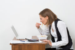 Girl eats a pasta, working behind the laptop Royalty Free Stock Photo
