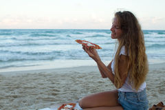 The girl eats pizza on the beach, a dinner at sunset, the girl fashionably dressed eats pizza. Stock Photos