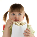 Girl eats popcorn and looks. Little girl on white background  eats popcorn in white paper package and looks to the right Stock Photo